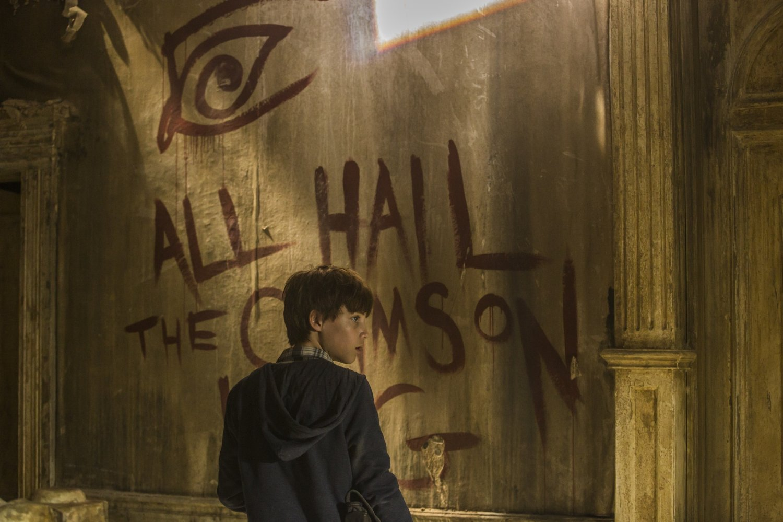 "Jake, de costas e olhando para o lado, e na parede a sua frente está escrito ""ALL HAIL THE CRIMSON KING"""