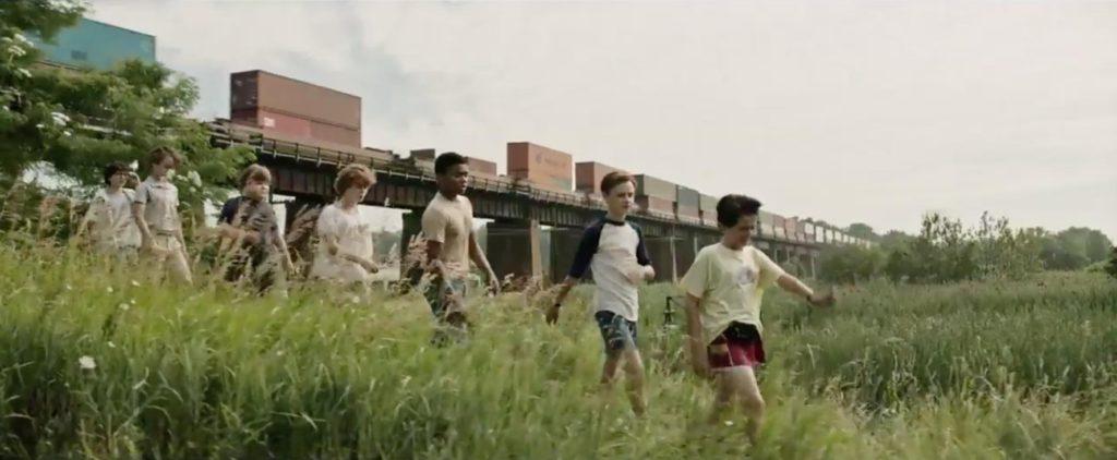imagem das 7 crianças andando num gramado, com um trem cargueiro passando ao fundo
