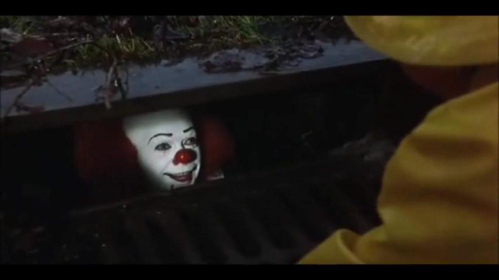 O palhaço Pennywise, dentro do bueiro, falando com o menino George (fora do quadro)